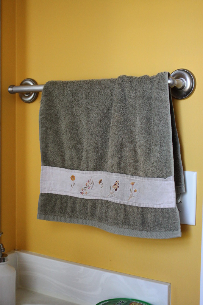 Beside the mirror. Towel hanger.