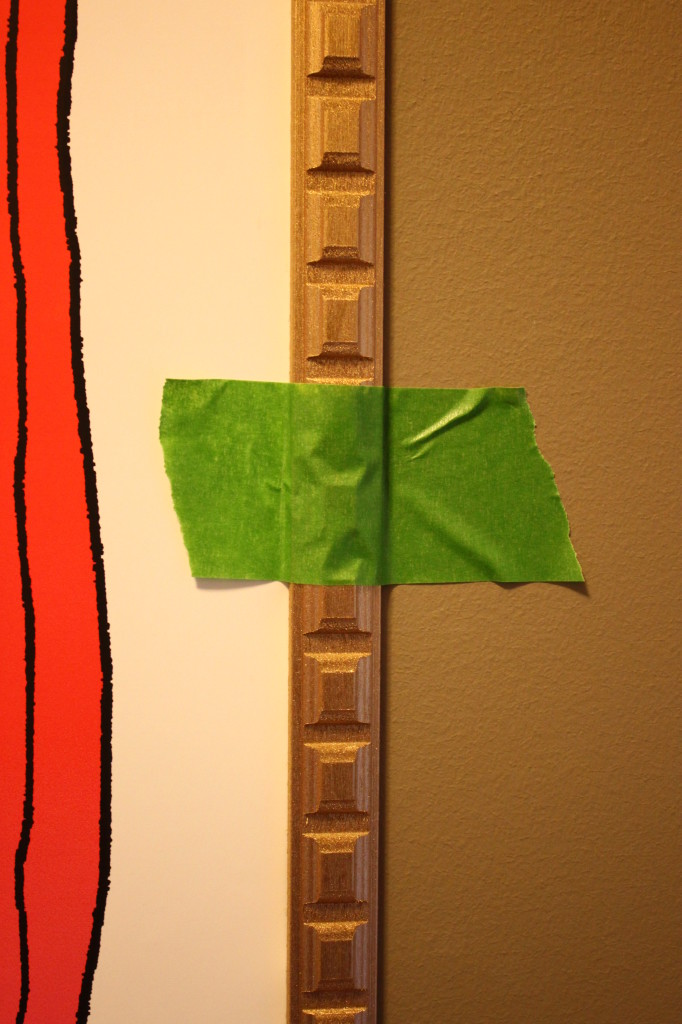 I attached the wood strips to both the print and the wall. Taped to hold them.